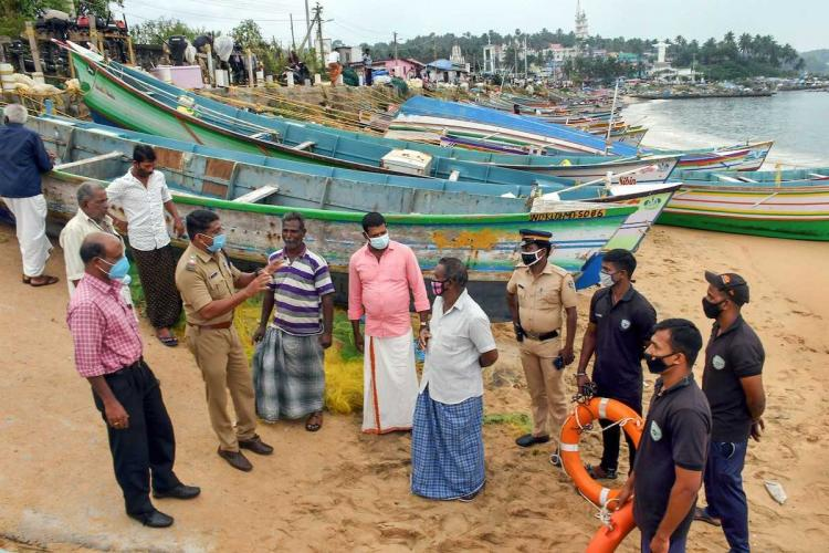 A few fishermen seen discussing preparations for Cyclone Burevi with the police and government officials on the seashore Several boats are can be seen tied up on the shore behind them