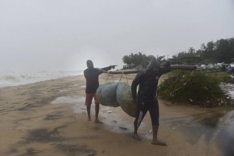 Photo of fishermen in Mamallapuram Tamil Nadu relocating their equipments to a safe place