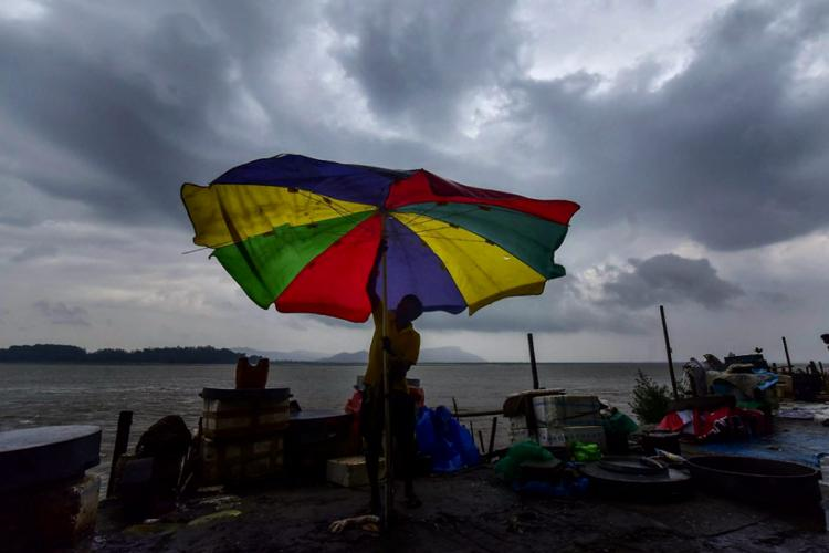 Cyclone representative A fish vendor struggles to hold onto his umbrella against the fast blowing winds with dark clouds seen above
