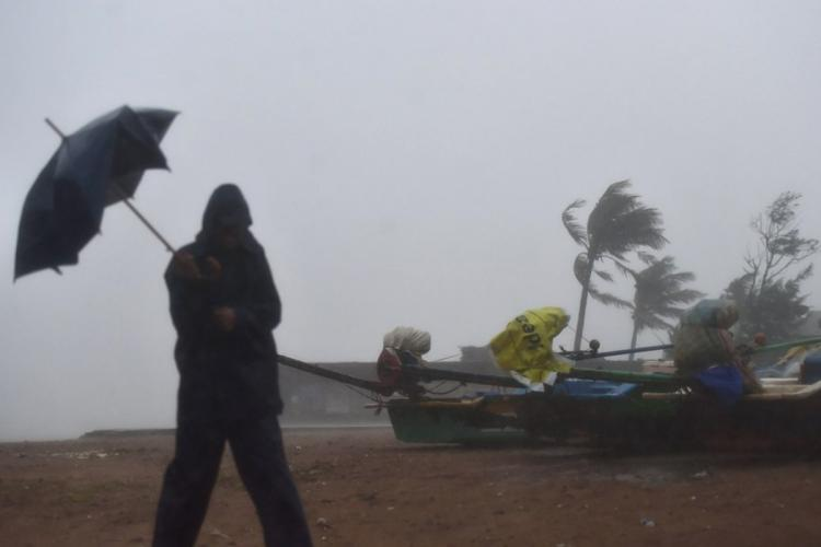 Silhouette of a man trying to hold an umbrella at a beach in heavy wind and rain with boats and coconut trees in the background