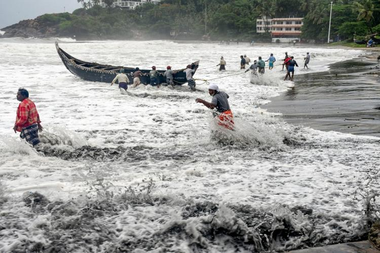 People pull a boat ashore which sailed away amid strong winds after a red alert in view of a cylonic formation in the Arabian Sea in Thiruvananthapuram