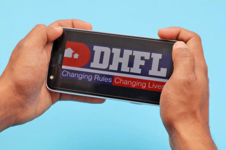 DHFL logo open on a phone person holding up phone