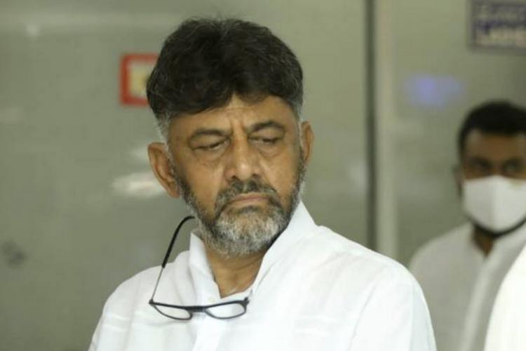 DK Shivakumar wearing a dejected look on his face He is wearing a white shirt with his glasses about his neck