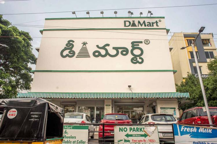 A Dmart supermarket in Hyderabad with the logo written in Telugu with a small logo in English at the top right Cars are parked in front