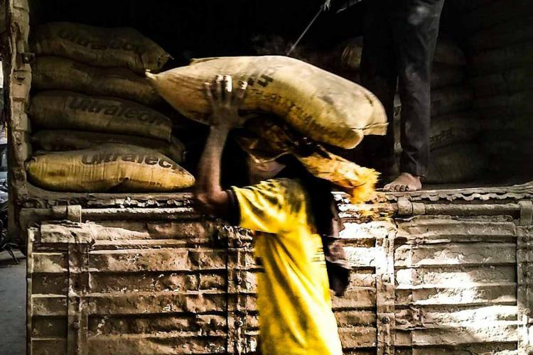 Daily wage worker carrying a bag of cement