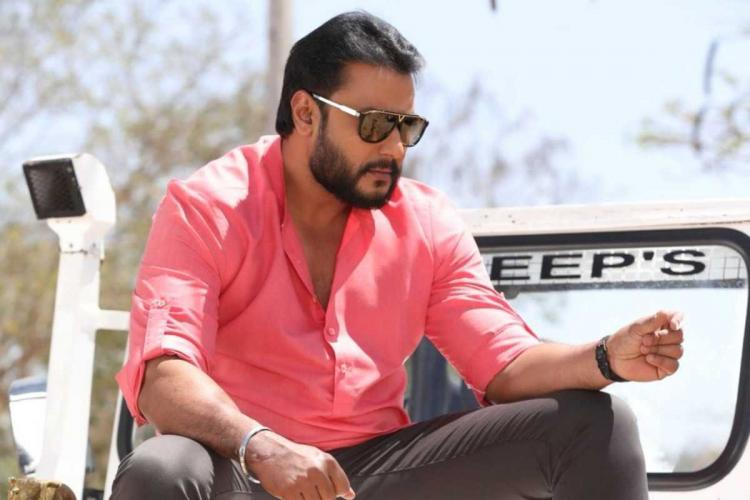 Actor Darshan posing wearing a pink shirt and grey trousers and sporting a pair of sunglasses