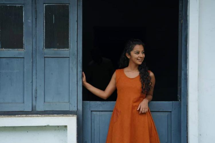 Darshana Rajendran is seen donning an tangerine dress in the image.