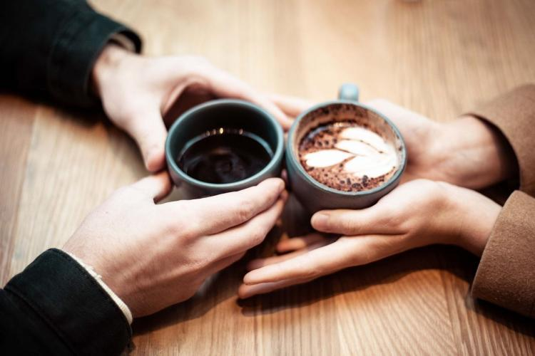 Two people with their palms around coffee mugs