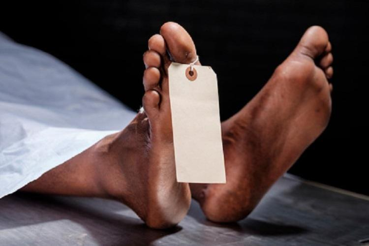A representative image of a deceased persons legs covered with a white sheet and a tag attached to the toe