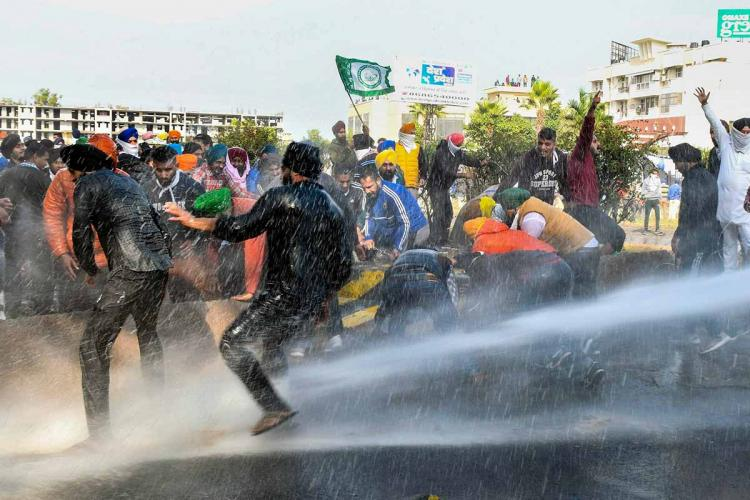 Protesting farmers being hit with water cannons by police