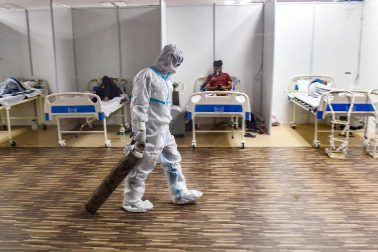 A doctor in PPE drags an oxygen cylinder at a Covid-19 Care Centre in New Delhi