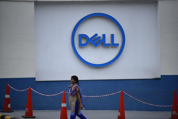 a woman walks in front of a Dell sign board