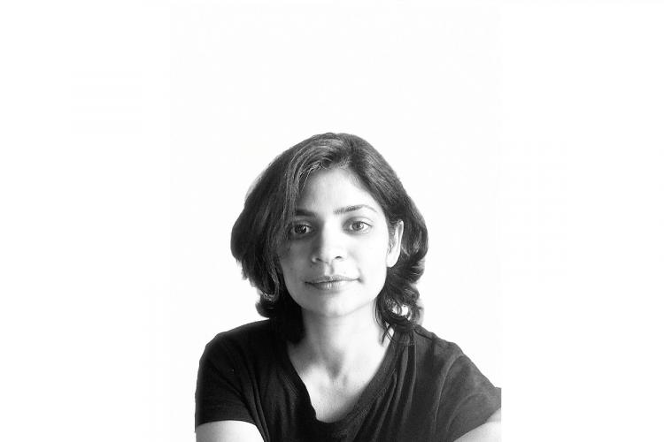 Devi in a black and white profile photo wearing a dark top her short hair falling forward on one side
