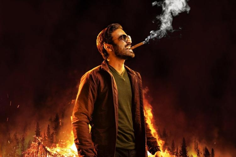 Dhanush smoling a cigarette in front of a burning house