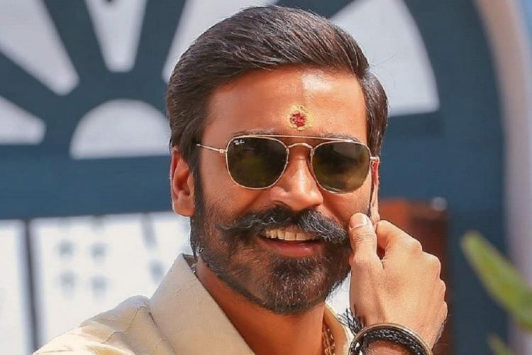 actor Dhanush is seen twirling his moustache