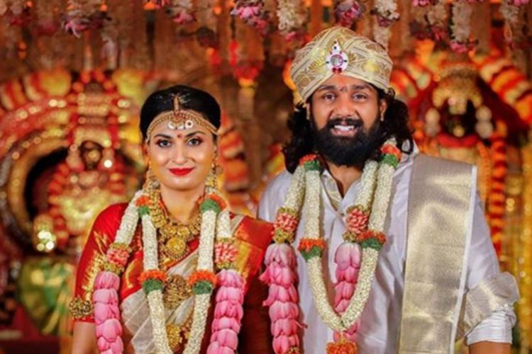 The wedding image of actor Dhruva Sarja and Prerana Shankar While Dhruva is geared up in traditional Kannadiga attire Prerana is decked up in a red sari Both have garlands on them