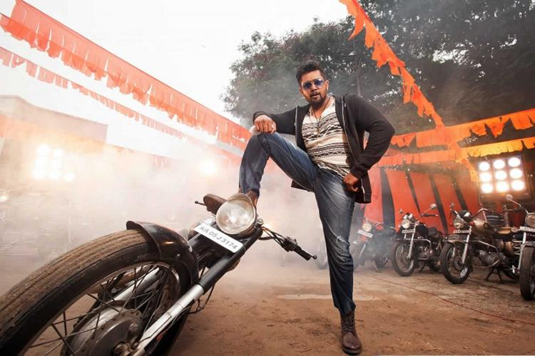 Actor Dhruva Sarja in jeans white t-shirt black jacket and dark sunglasses posing with one leg propped up on a motorbike