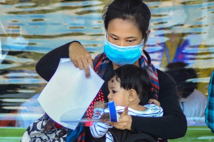 woman traveller with her child is processing papers with a face mask on