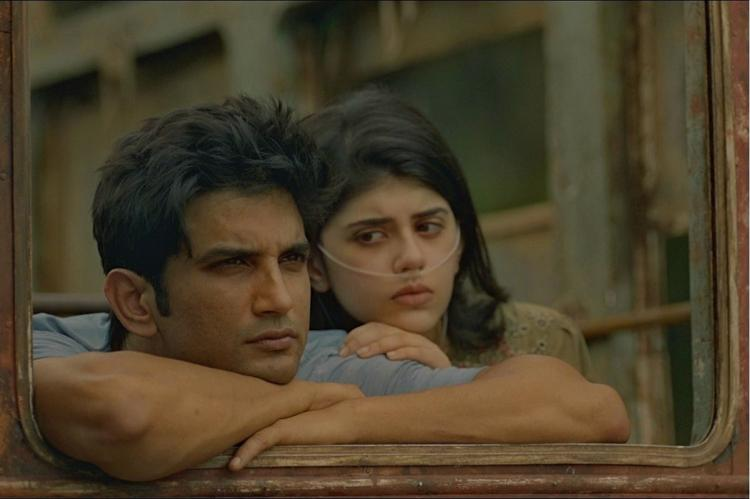 Sushant Singh Rajput and Sanjana Sanghi in Dil Bechara Sanjana sits behind Sushant who is leaning against a window frame