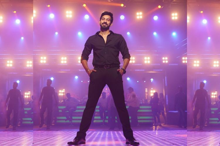Director Santhosh in black shirt and pants standing on the dance floor of a pub
