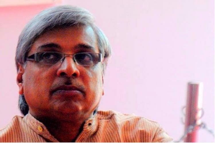 Kamal with light coloured shirt and specs and mostly grey hair against a pink background