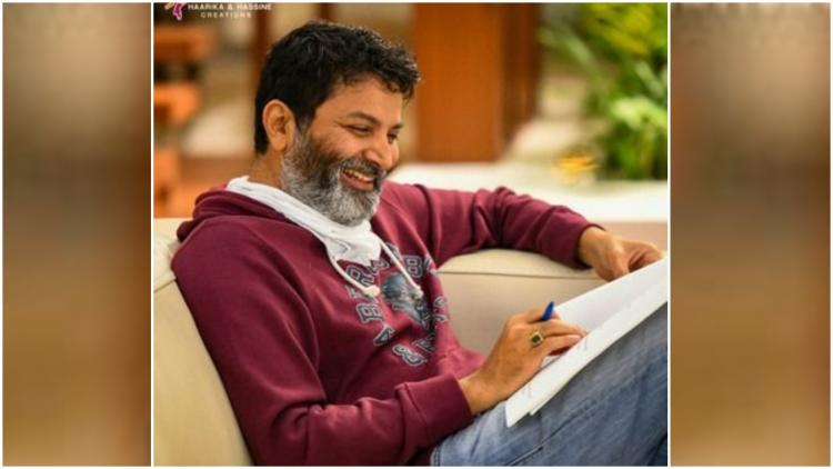 Trivikram Srinivas writing something in his book by wearing a brown shirt and a jeans pant