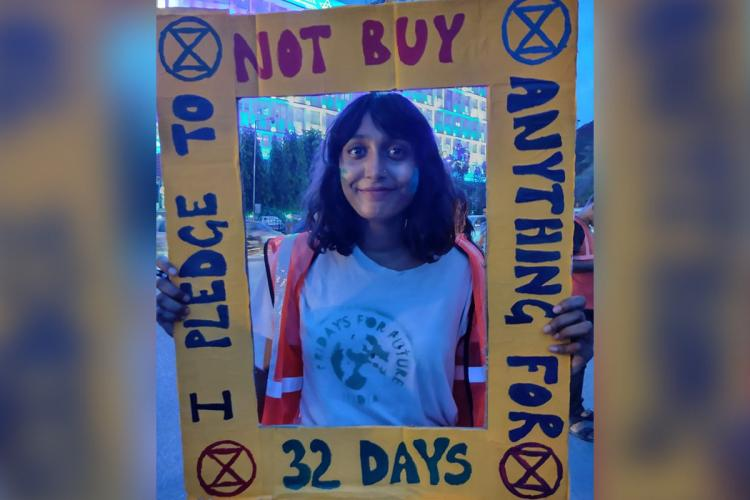 Climate change activist Disha Ravi holds a frame and poses for a photo