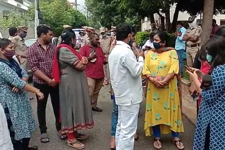 Family members of the Hyderabad veterinarian who was gangraped and murdered in 2019 standing outside Ram Gopal Vermas residence where some police officials can also be seen standing