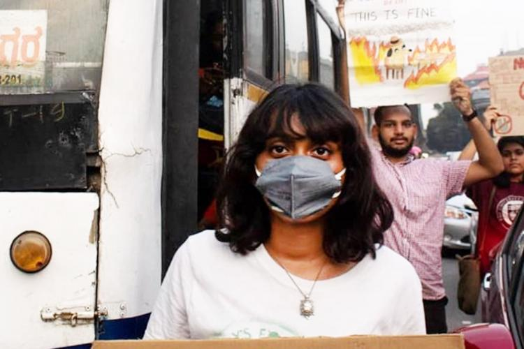 DDisha Ravi wearing a mask and standing in front of a bus