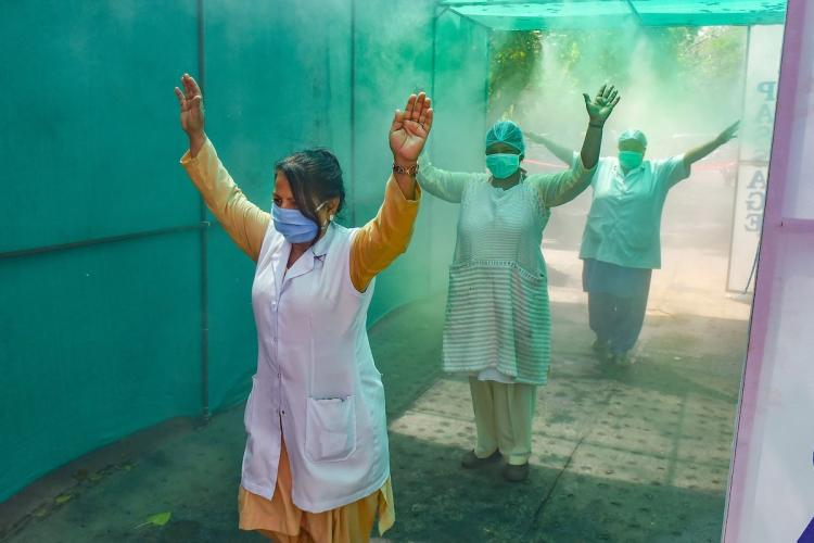 Medics walk through a newly-constructed sanitizing tunnel at Hindu Rao Hospital during the nationwide lockdown to curb the spread of coronavirus in New Delhi Sunday April 12 2020 Isolation wards have been set up at the hospital to treat COVID-19 patients