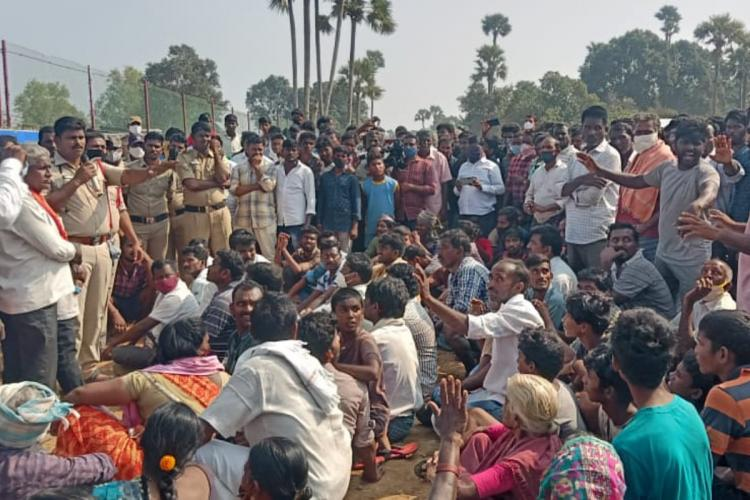 A large crowd sitting in protest on road while a police officer holding a mic tries to negotiate with them