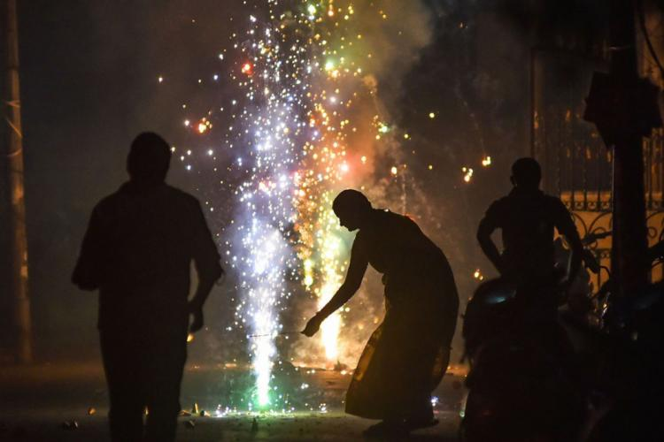 Silhouettes of people lighting firecrackers on Diwali