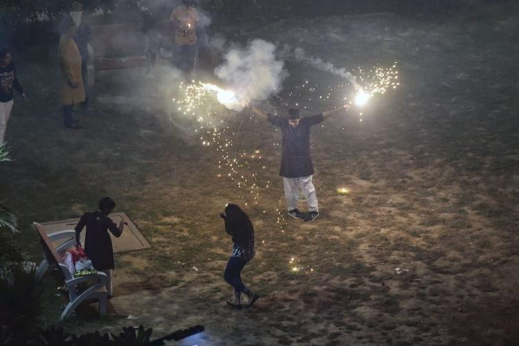 Smoke rises as people burn crackers during Diwali celebrations, in New Delhi, Sunday, October 27, 2019.