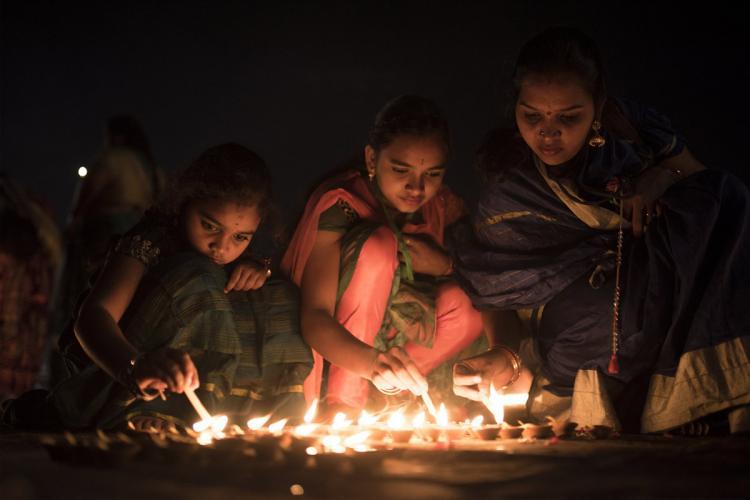 People lighting diya for Diwali