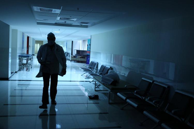 Silhouette of a doctor walking along a desolate corridor