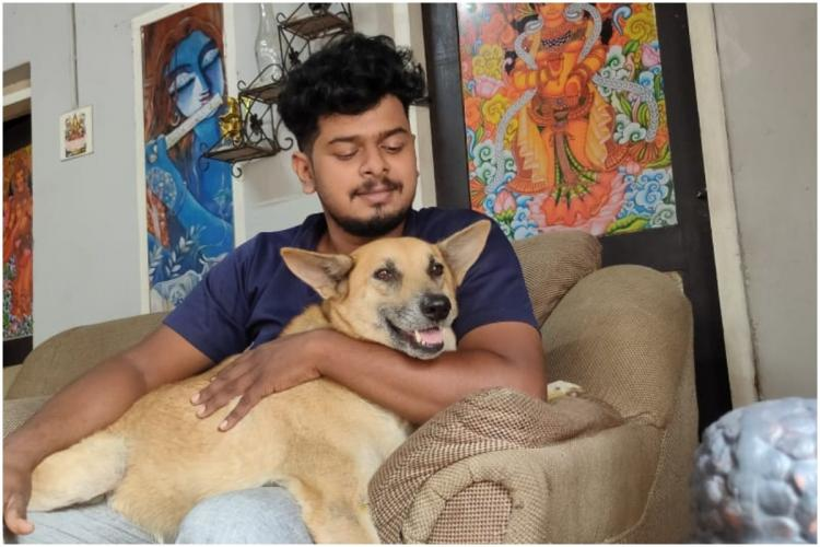 Dog sitting on the lap of an animal rescuer on a couch against the background of wall paintings