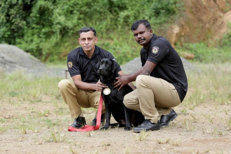 Dog squad Dona with her trainers Aneesh and Pradeep