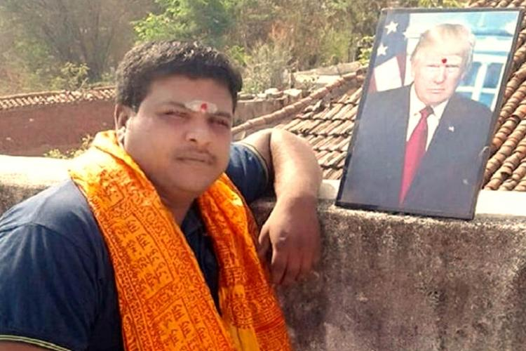 Telangana native B Krishna wearing a orange scarf standing next to a photoframe of US President Donald Trump