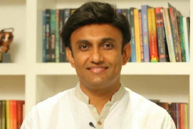 Dr K Sudhakar wearing a white shirt There is a bookshelf behind him