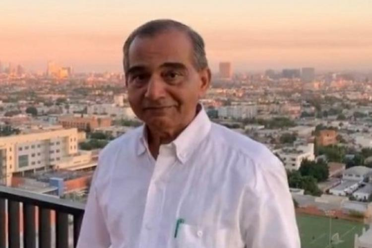 Dr Keshava Bhat in a light colour shirt stands at a balcony while a city and its buildings can be seen in the background