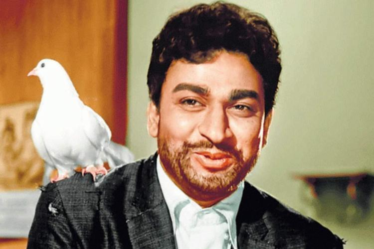 Dr Rajkumar is seen wearing a black coat and is seen along with a white dove