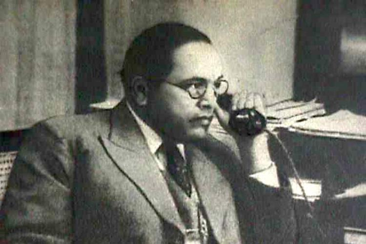 A photo of Dr BR Ambedkar holding a phone to his ear and looking to the right of the frame Photo is from Velivadacoms archives of original photos of Dr BR Ambedkar
