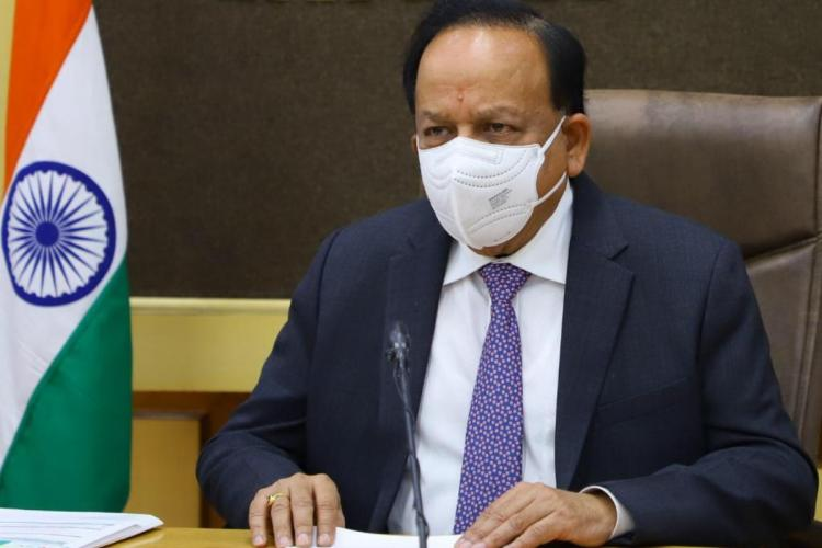 Union Health Minister Dr Harsh Vardhan wearing a white shirt blue suit white mask and sitting at a table