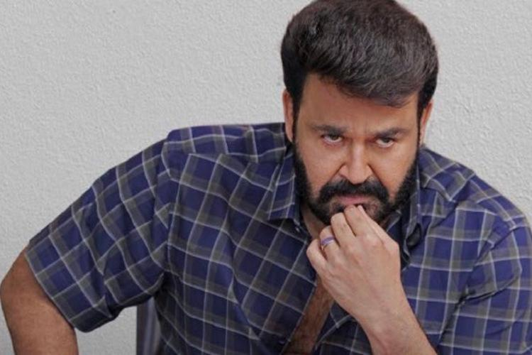 Mohanlal wearing a check shirt of navy blue and violet has a beard and sits with a thoughtful expression a hand on his chin