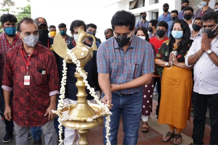 Director Jeethu Joseph, wearing a black face mask, is seen lighting a lamp at the pooja of the Drishyam 2 film shooting. He is wearing a checked shirt and a pair of jeans. Other members of the cast and crew can also be seen in the image. Most of them are wearing masks and hand gloves.