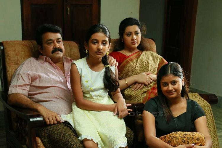 Still from Malayalam film Drishyam with Mohanlal Meena Esther and Ansiba sitting in a drawing room