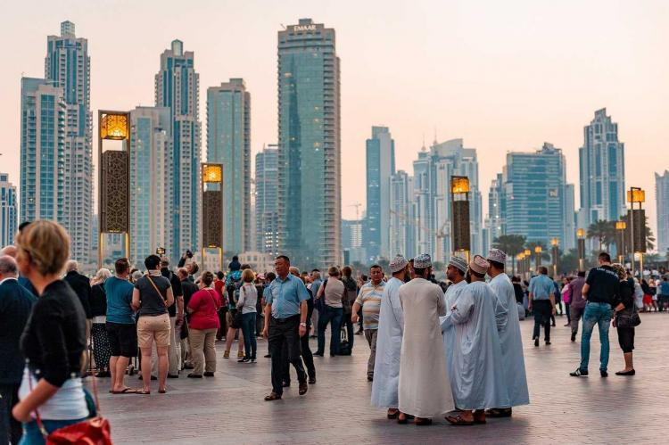 A photo of downtown Dubai showing several tall buildings in the background and people in the foreground