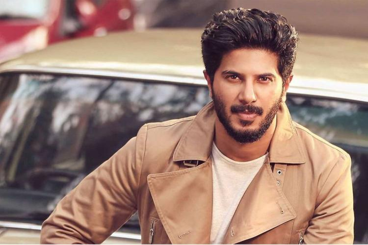 Dulquer wearing a white t shirt and a brown overcoat resting against a car