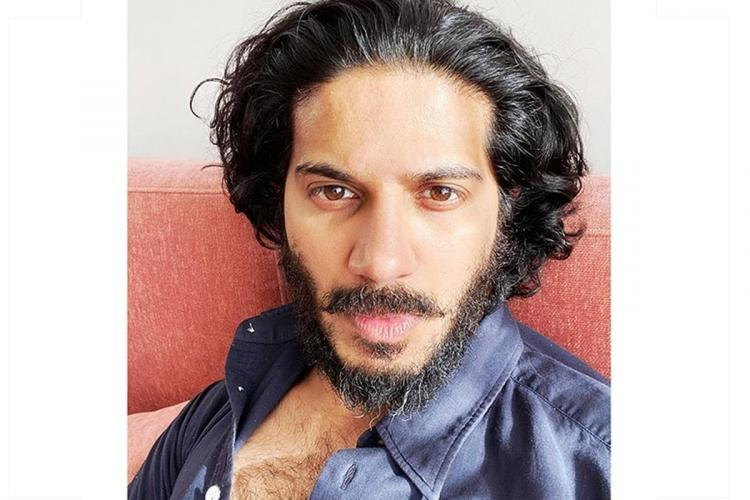 Dulquer with his long hair and beard in a blue shirt