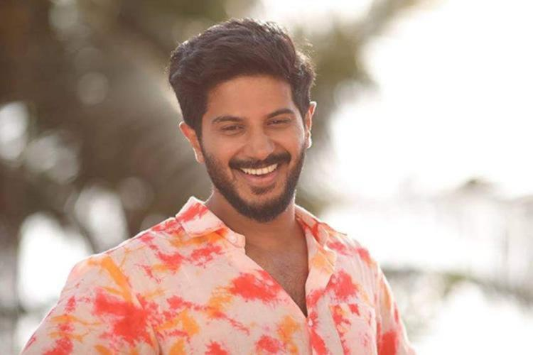 Dulquer Salmaan in a white pink and orange shirt smiling with blurred trees in the background